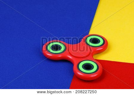 Red fidget spinner lying on multicolored background