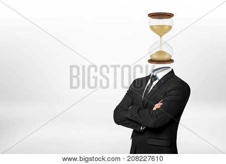 A businessman with his arms folded in front stands on white background and has his head replaced with a hourglass. Working hours. Schedule and planning. Multitasking.