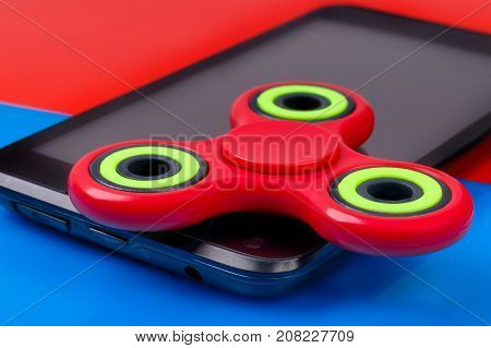 Close-up shot of red fidget spinner lying on smartphone. Selective focus