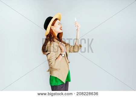 girl in a hat makes selfie on a white background