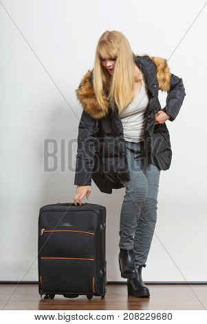 Young woman in warm jacket with suitcase. Gorgeous blonde tourist travel girl. Tourism.