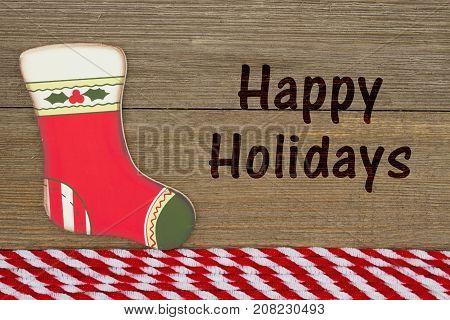 Old fashion Christmas greeting A retro Christmas stocking on weathered wood background with text Happy Holidays