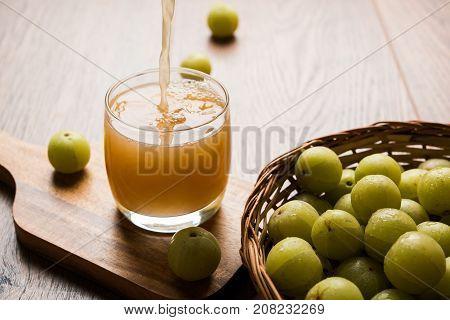 Indian fresh gooseberry juice or stock photo of Amla juice (Phyllanthus emblica) , selective focus