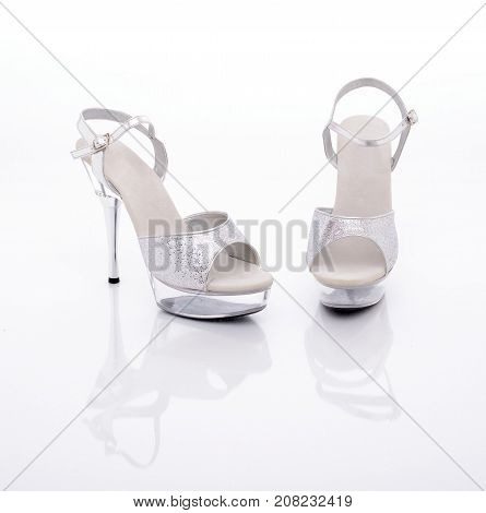 Silver high heel stripper shoes on white background