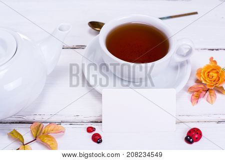 black tea in a round white cup with saucer and brewer ahead of an empty white paper square business card