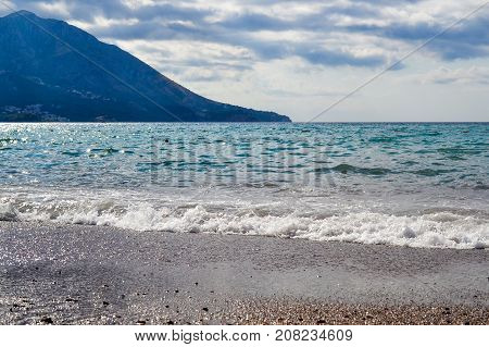 Sea view in inclement weather. Low clouds over the coast. Montenegrin beach in rainy weather. The sea and mountains of Montenegro. Budva. Becici