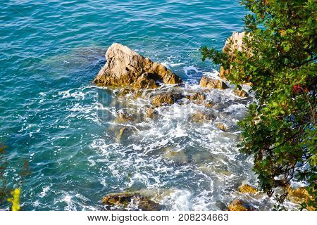 Huge stones in the sea and waves. On a sunny day. View from above. Montenegro. The Budva Riviera