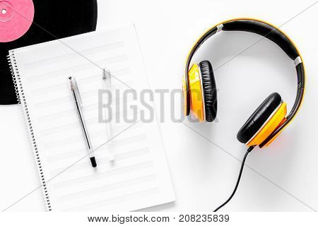 Worktable of composer today. Headphones, vinyl record, music notes on white background top view.