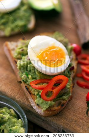 Healthy breakfast- sandwich prepared with organic bread, guacamole, pepper and boiled chicken egg