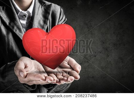 Cropped image of businessman in suit presenting big red heart his hands with dark wall on background. 3D rendering.