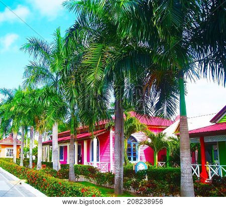 Green territory of the Gran Banya Luxor hotel in Punta Cana. Colorful houses and buildings in Dominican Republic