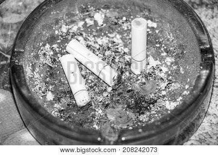 Three cigarette butts in the dark ashtray. Black and white photo