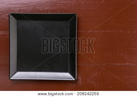 Flat Lay Above Black Square Plate On The Brown Wooden Table Boards