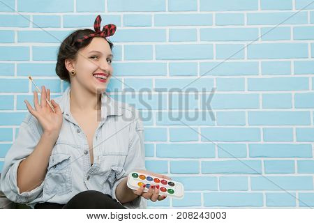 woman the artist draws bricks on a wall paints for drawing