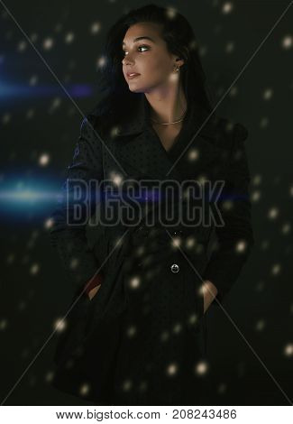 Young woman in a coat for autumn winter fashion with snow