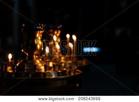 Blurred image of burning wax candles in the Christian Russian Orthodox Church. Background for religious topics. Selective focus