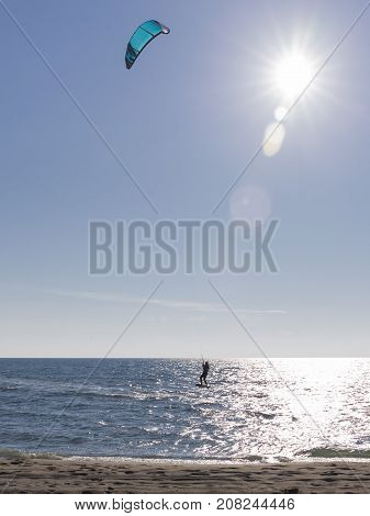 The unrecognizable kitesurfer rides on sea water on a board with a blue kite in bright sunlight and glare on the water