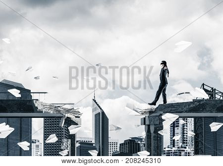 Businessman walking blindfolded among flying paper planes on concrete bridge with huge gap as symbol of hidden threats and risks. Cityscape view on background. 3D rendering.