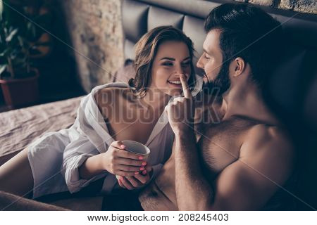 Enjoy each other mug of tea and the morning. Two young lovers are cuddling in the bed looking deep into eyes of each other guy plays with her true love feelings emotions poster