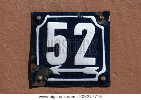 Weathered grunge square metal enameled plate of number of street address with number 52 closeup