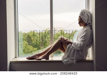 girl in a Bathrobe and towel on head sits on the window sill on the highest floor of the hotel