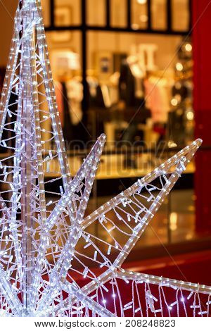 Close-up of piece of large decorative Christmas star on background of bright shop windows. Generous and rich Christmas.