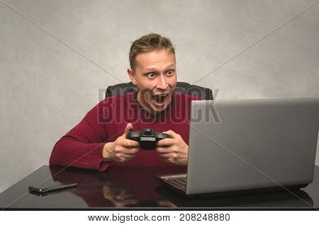 Emotinal gamer young man goes crazy when playes in game. Young hysterical man with joystick.