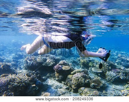 Snorkeling girl with underwater camera in coral reef. Snorkel with camera in underwater housing. Snorkeling in full face mask. Summer holiday. Beautiful girl in water. Tropical seashore landscape