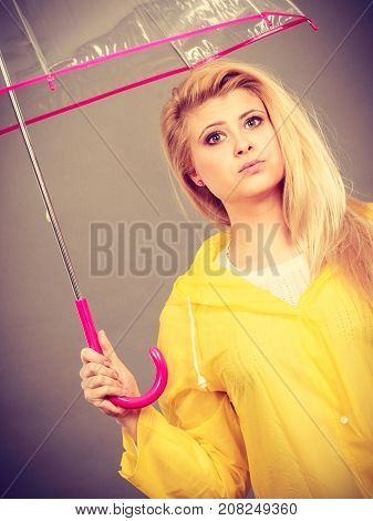 Sad bored blonde woman wearing yellow raincoat holding transparent umbrella waiting for rain.