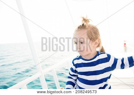 Boy sailor with blond hair ponytail in striped shirt sailing on blue sea water. Summer vacation concept. Travel adventure discovery wanderlust. little sailor man concept