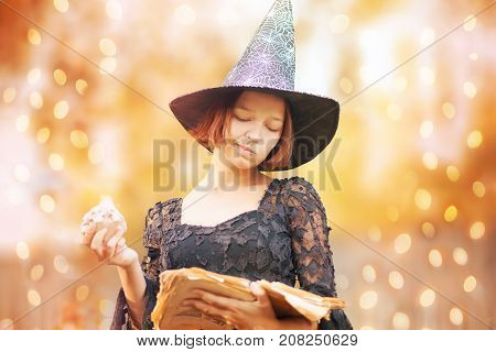 Young woman dressed like a witch ready for halloween looking at the spell book. Fall outdoors happy halloween art photo.
