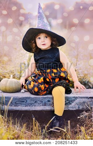 Toddler girl ready for halloween and trick or treat. Adorable little witch. Toned in blue and yellow happy halloween art photo.