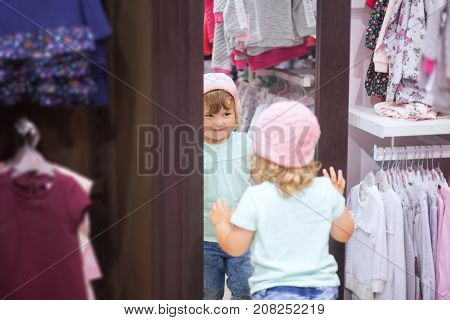 Adorable toddler girl in baby apparel store looking at the mirror choosing clothes fitting warm autumn knitted hat cute little shopper.