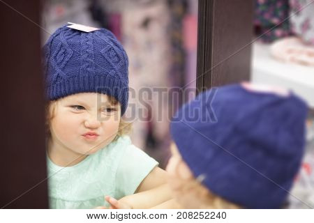 Cute Little Girl Choosing Clothes In The Shop, Fitting Knitted Hat.