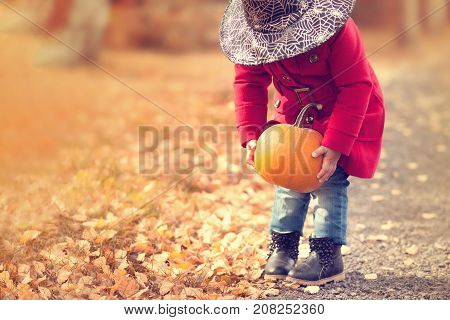 Little girl wearing Halloween witch hat and warm red coat having fun in the park at autumn day. Little orange pumpkin happy laughing child. Toning toned photo copyspace empty space for text