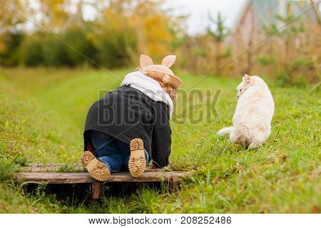 Cute funny little girl walking with her cat best friends kid and pet having fun together outdoors beautiful fall day childhood and friendship.