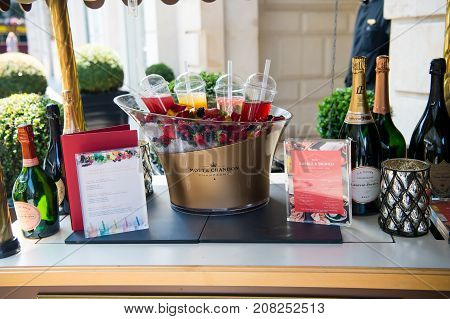 Paris France - June 01 2017: bar counter outdoors on building background. Menu champagne bottles fresh berries on ice and coctails on table. Buffet brunch luxury hotel concept.