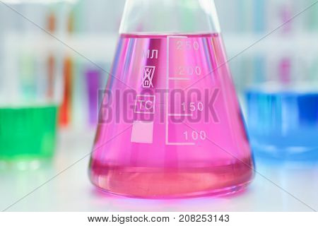 Chemical industry bulb with blue magenta pink liquid lab tubes stand on the table in the laboratory of liquid testing test development substances poisons additives stabilizers flavors house cleaning