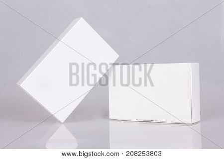 Two tall white boxes whith reflection. Mockup ready for your design. Box perspective. Box template. Box empty blank. Box software. Gray background.