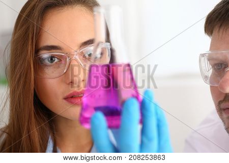Female and male chemist holds test tube of glass in his hand overflows liquid solution of potassium permanganate conducts an analysis of water samples versions of reagents using chemical manufacturing