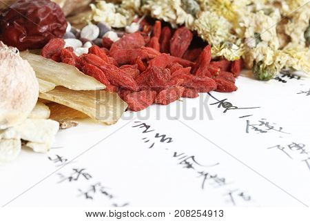Chinese herbal medicine elements on the recipe paper (The Chinese characters are a list of herbal names, which form a recipe, written by the photographer.)