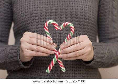 Detail of female hands holding two candy canes forming heart shape. Focus on the top of the candy cane