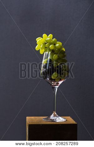 A food photo combines incompatible images. Brushes of red and green grapes in a wine glass look aristocratic and provocative. A top view of a gastronomic ecstasy. Perfect shot