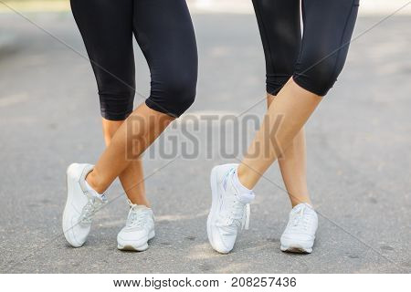 Close-up of legs in black leggings and comfortable sports sneakers on a blurred background. Two athletic slim girls in sportswear.