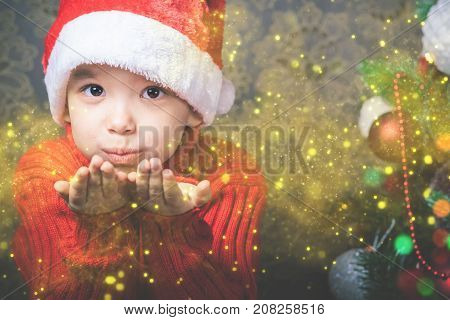 Little boy fairy blowing fairy magical glitter, stardust at Christmas. Christmas tree. Xmas child and New Year holiday. Merry Cristmas your family