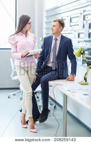 Young business partners make a business plan. A girl with glasses writes everything down on paper. The man is sitting on the table. Close-up.