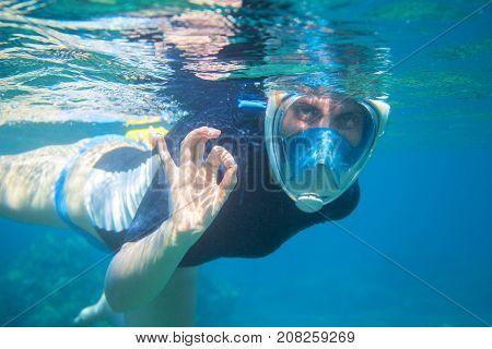 Snorkel girl underwater shows ok gesture. Snorkeling in full face mask. Summer activity. Beautiful girl in water. Underwater photo of ocean landscape. Active seaside vacation. Snorkeling in tropic sea