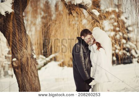 A Beautiful Ginger Bride In A White Fur Coat And A Groom Are Hugging In The Snowy Park. Winter Weddi