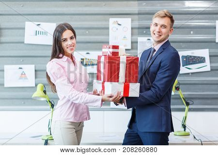 Young happy employees are standing with gifts in the office. They look at the camera. Close-up.