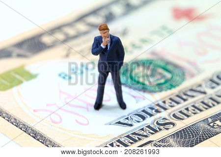 Businessman figurine on usa dollar banknote. Business standing on money concept. Modern economics and financial growth. Thinking businessman. Profitable business strategy. Business growth and manager